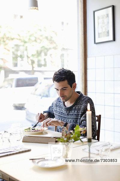 Junger Mann am Restauranttisch beim Essen mit digitalen Tabletten
