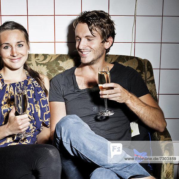 Paar mit Champagnerflöten auf Sofa im Salon