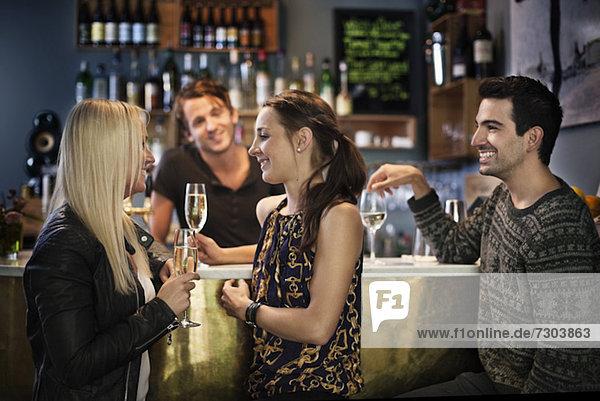 Seitenansicht der Freunde lächelnd  während die Bar zärtlich auf sie schaut