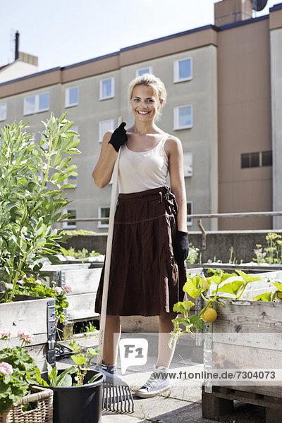 Porträt einer glücklichen jungen Frau mit Gartengabel im Stadtgarten