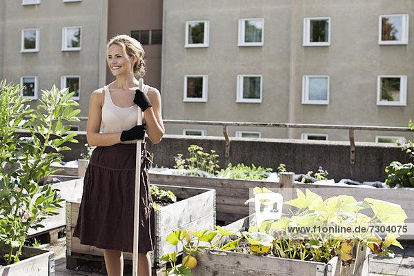 Fröhliche junge Frau schaut weg  während sie im Stadtgarten steht.