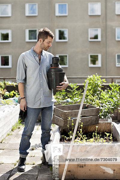 Junger Mann mit gestapelten Blumentöpfen am Stadtgarten stehend