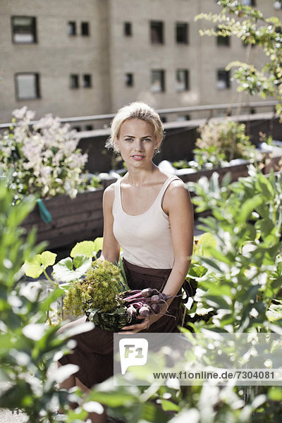 Porträt einer jungen Frau,  die im Stadtgarten sitzt.