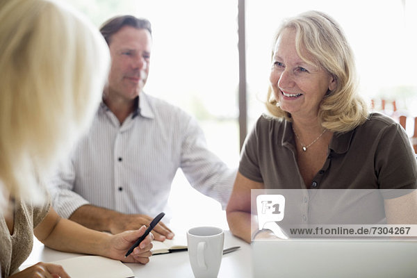 Glückliche Frau mit Kollegen beim Geschäftstreffen