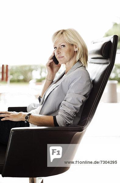 Reife Geschäftsfrau beim Sitzen in der Bürolobby per Handy