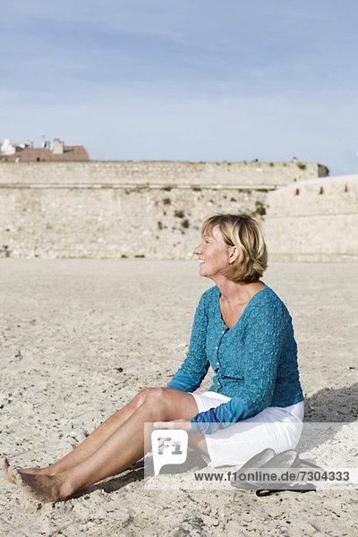 Volle Länge der glücklichen Frau  die auf Sand am Strand sitzt.