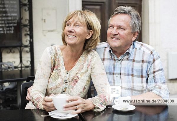 Ein glückliches Paar beim Kaffeetrinken beim Blick auf den Tisch