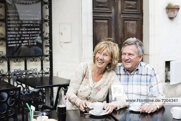 Ein glückliches Paar schaut weg  während es am Tisch Kaffee trinkt.