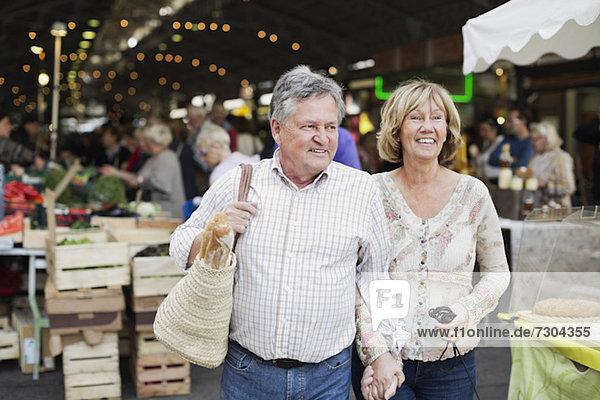 Glückliches Paar schaut weg mit Markt im Hintergrund