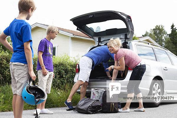Glückliche kaukasische Familie beim Verladen des Gepäcks im Kofferraum zum Picknick