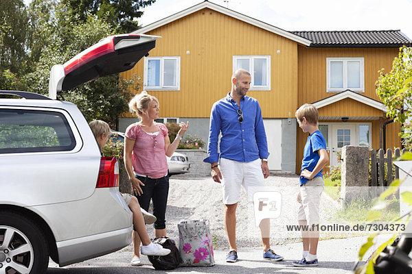 Kaukasische Familie im Gespräch mit dem Auto beim Picknick