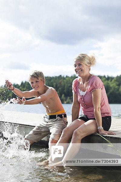 Fröhliche reife Frau am Pier sitzend mit Sohn  der Wasser spritzt.