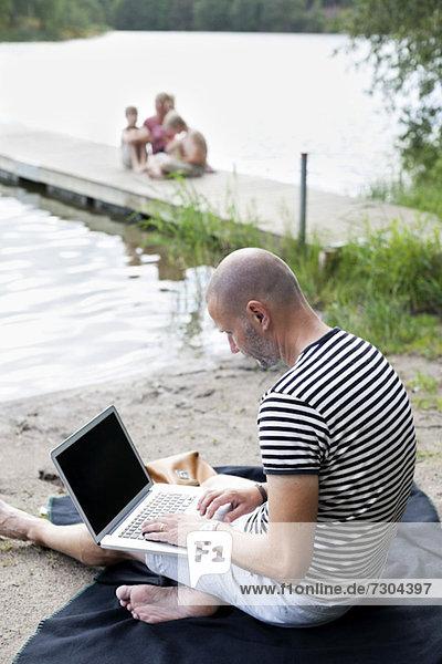 Erwachsener Mann mit Laptop am Strand mit Familie auf dem Pier sitzend