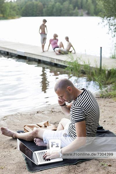 Reifer Mann mit Laptop bei der Kommunikation auf dem Handy am Strand mit der Familie am Pier sitzend