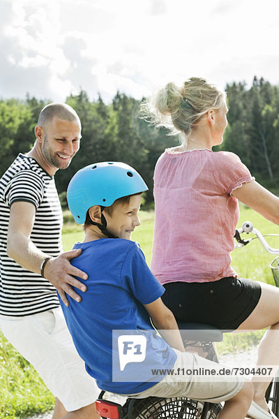 Mann schaut auf den Sohn  der hinter der Frau auf dem Fahrrad im Park sitzt.
