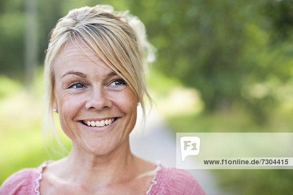 Nahaufnahme einer fröhlichen reifen Frau  die zur Seite schaut