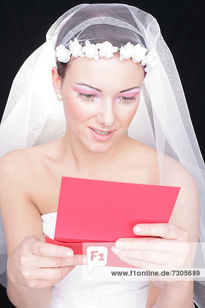 Bride reading from a red paper