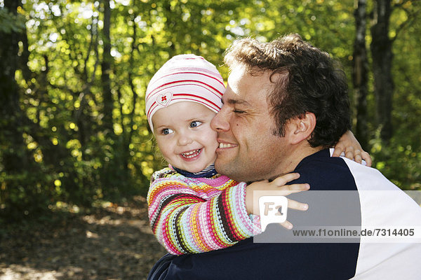 Father and his three-year-old daughter  hugging