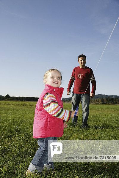 Vater und Tochter (3 Jahre) spielen mit einem Drachen