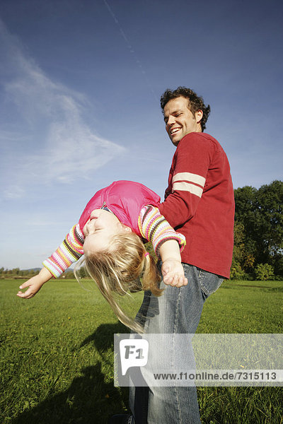 Father and his three-year-old daughter playing airplane
