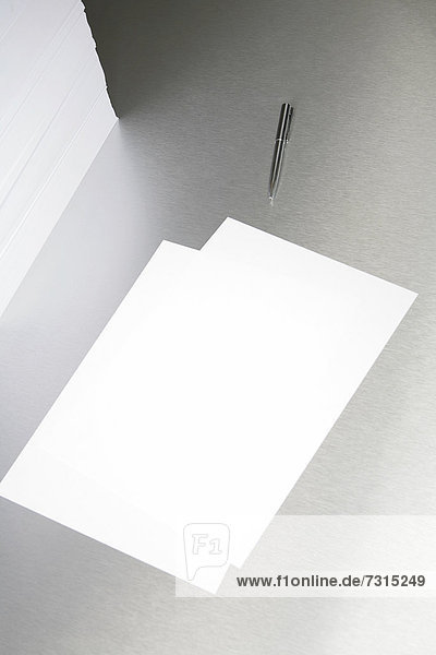 Silver desktop with pen and sheets of paper