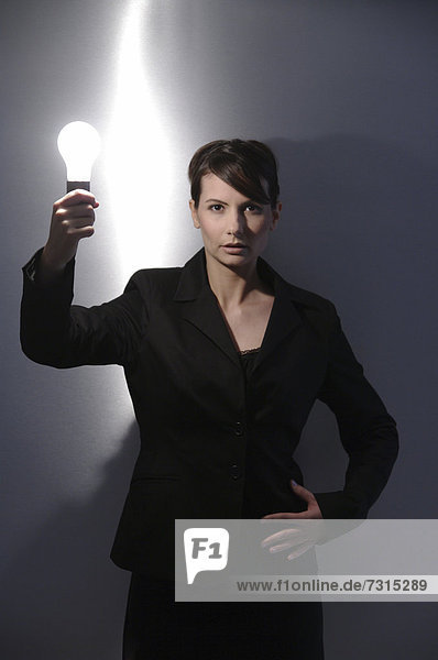 Businesswoman  aged 24  with a light-bulb in her hand