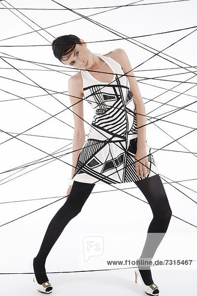 Woman  24  dressed in the style of the 60s  standing between spanned threads  symbolic image network