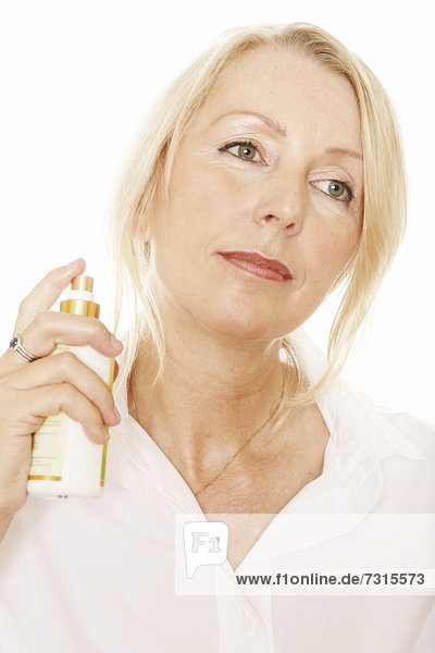 Woman  49  spraying herself with a perfume bottle
