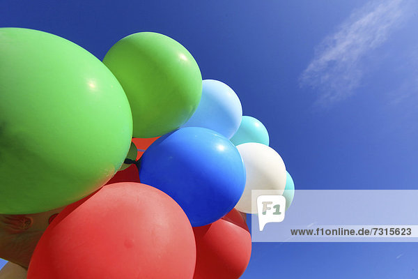 Many colourful balloons against a blue sky