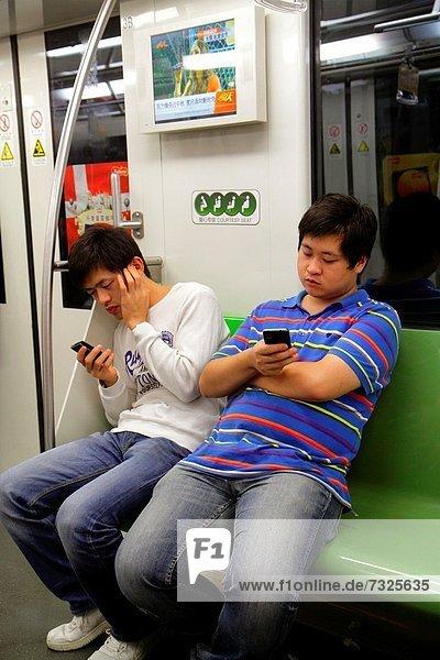 Mann  Kurznachricht  fahren  Öffentlicher Verkehr  U-Bahn  Metro  China  Shanghai