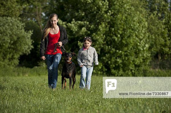 Zwei Mädchen laufen mit einem Dobermann über eine Wiese