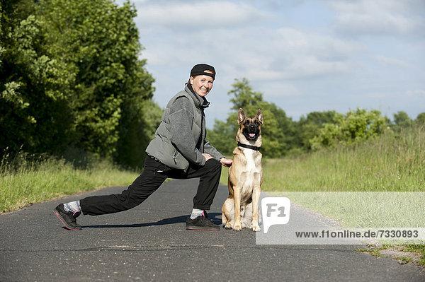 Frau joggt mit Malinois  hier beim Dehnen