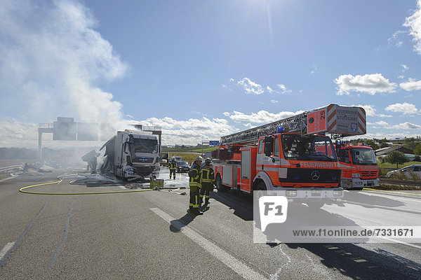 'Firefighters extinguishing a truck fire on the A8 motorway near the ''Echterdinger Ei'' junction  Stuttgart  Baden-Wuerttemberg  Germany  Europe'
