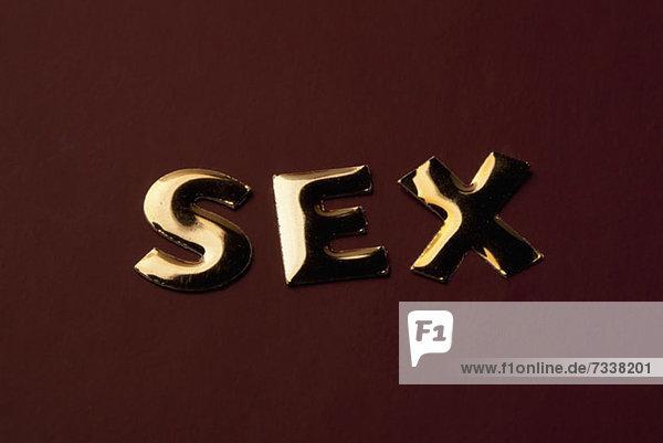 Das Wort'Sex' in goldenem Schriftzug