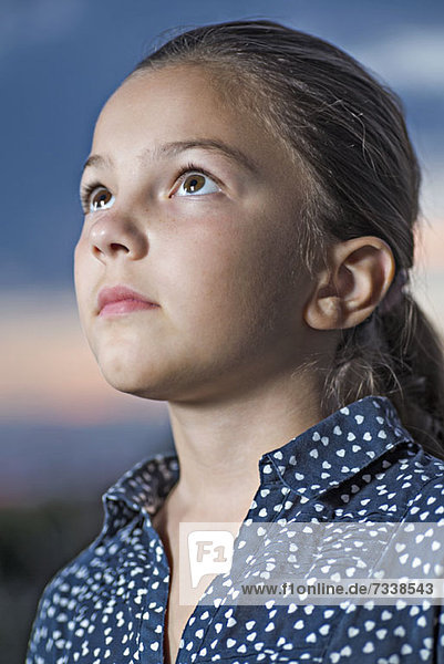 A girl looking up contemplatively  close-up