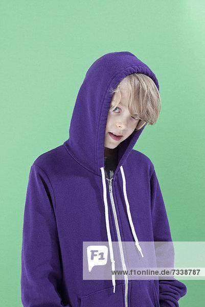 Ein Junge mit der Kapuze seines Sweatshirts  der schüchtern in die Kamera guckt.