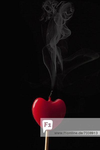 Rauch aus einer erloschenen herzförmigen Kerze am Stock