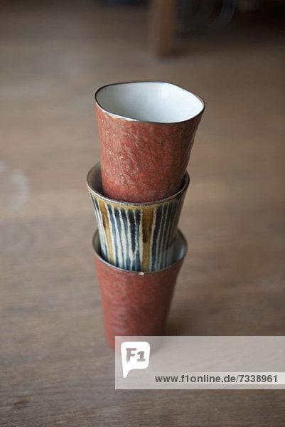 Drei gestapelte Tassen auf einem Holzboden