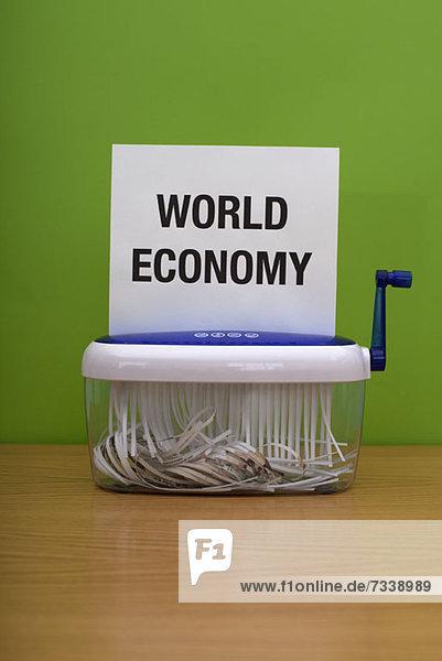 Worte'Weltwirtschaft' durchlaufen eine Zerkleinerungsmaschine