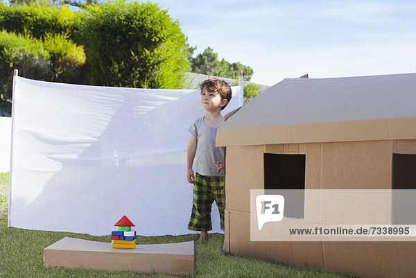 Kind steht neben Pappspielhaus
