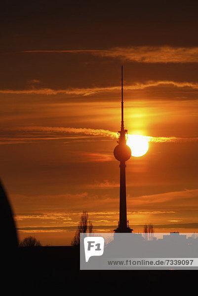 Der Fernsehturm am Alexanderplatz  der sich vor einem wunderschönen Himmel mit Sonnenuntergang abhebt.