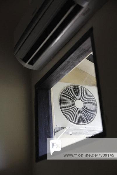 Ein elektrischer Ventilator durch ein Fenster gesehen  Blickwinkel niedrig