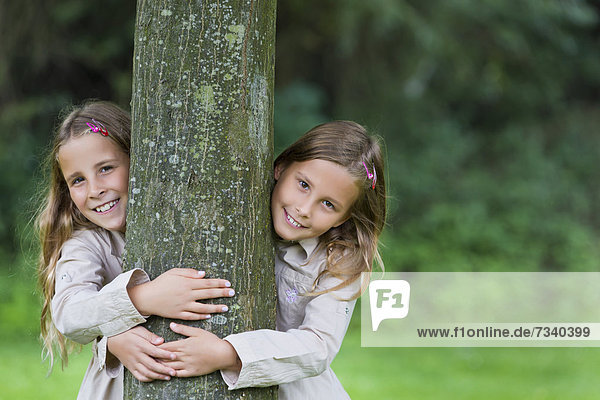 Twin girls  9  looking from the left and the right behind a tree