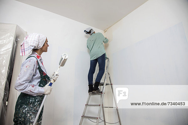 Mother and daughter renovating a room  painting the walls with paint rollers