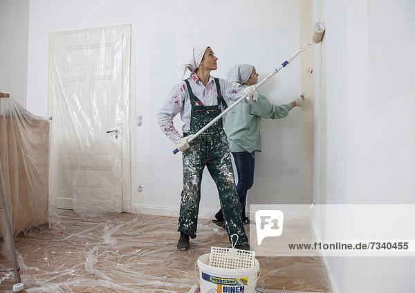 Mutter und Tochter renovieren ein Zimmer  streichen Wände mit Farbrollen