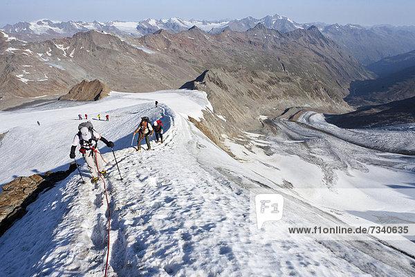 Wanderer auf dem Grat  beim Aufstieg zum Similaun auf dem Niederjochferner im Schnalstal  hinten der Marzell-Kamm  Südtirol  Italien  Europa