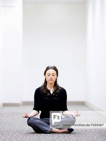 businesswoman sitting on the floor meditating