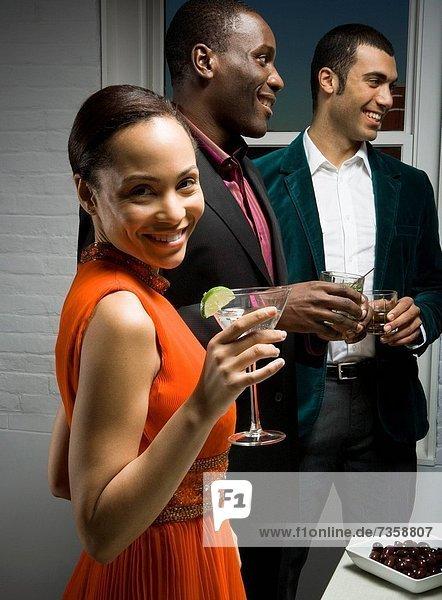 stehend nebeneinander neben Seite an Seite junge Frau junge Frauen Portrait Mann Glas Wein halten Mittelpunkt 2 Erwachsener