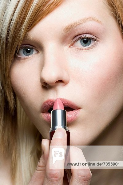 Portrait of a young woman applying lipstick