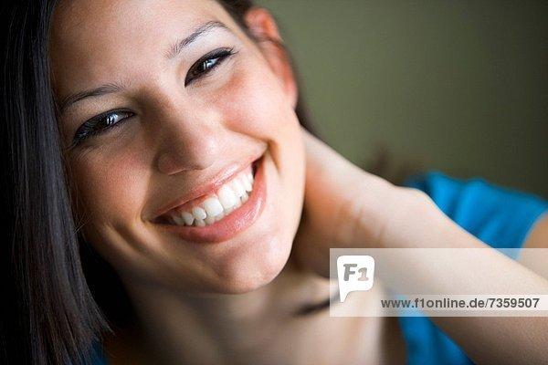 Portrait einer jungen Frau mit der Hand auf ihrem Hals